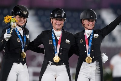 Germany's Dorothee Schneider, Isabell Werth and Jessica von Bredow-Werndl celebrating Dressage team gold at the Tokyo 2020 Olympic Games in Baji Koen Equestrian Park today. (FEI/Shannon Brinkman)